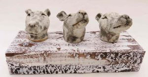 ceramic dogs, whippet heads on woodblock